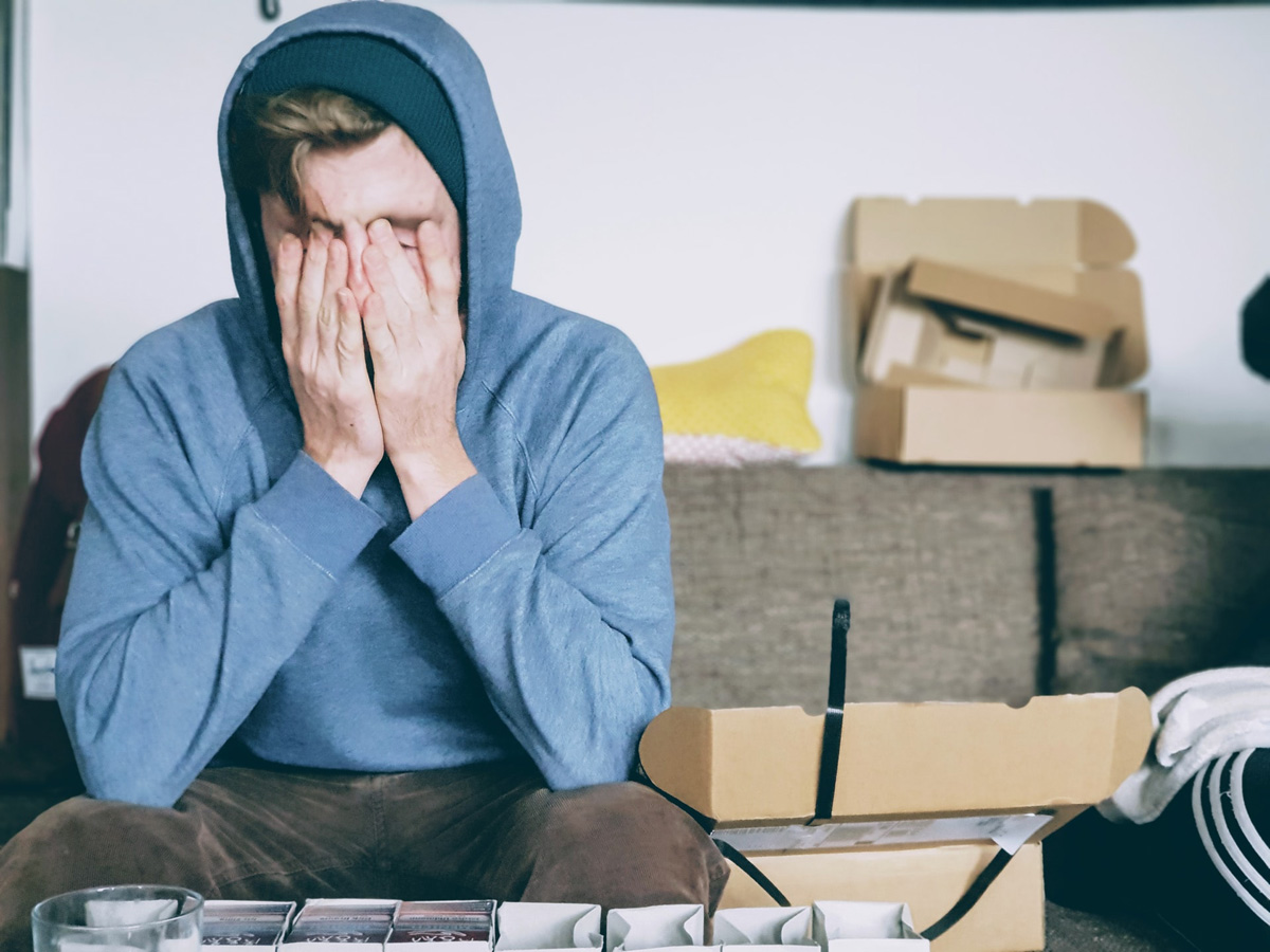 Photo of many in hoodie sitting on couch with face in hands.