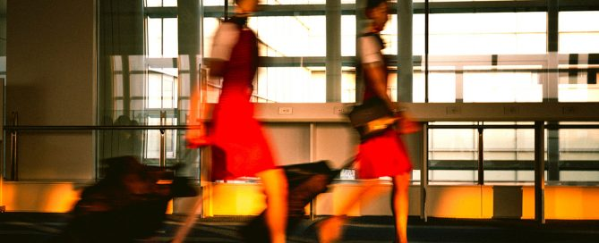 Photo of two flight attendants moving through an airport. Photo by Naitian(Tony) Wang on Unsplash