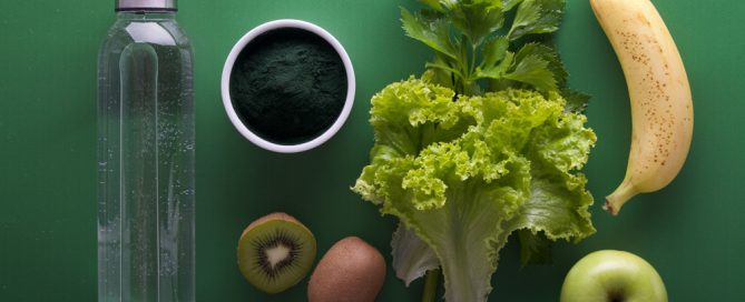 Picture of a water bottle, spirulina, one and a half kiwi, lettuce, and apple and a banana on a green background.