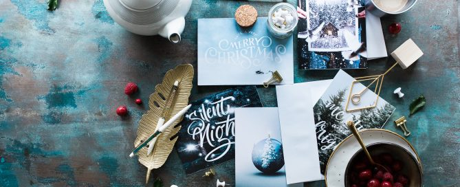 Image of holiday cards, pens and teapot with tea cup.