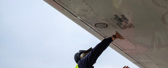 Image of aircraft technician in a yellow vest working under a wing