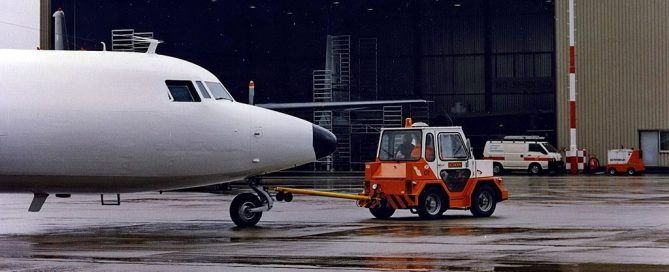 Image of maintenance workers towing a plan in front of the schreiner aircraft maintenance hanger.