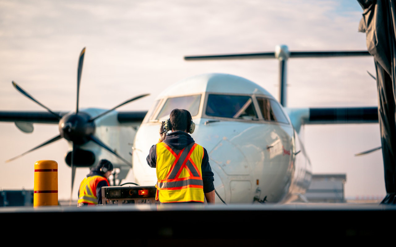 Image of a man in a visibility vest and headphones standing in front of a plane