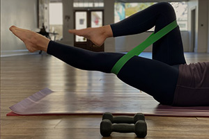 Image of person in leggings exercising on the floor with a tension band around legs.