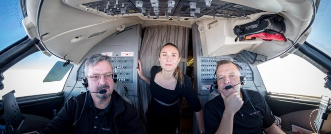Picture of flight attendant and pilots in the cockpit of an aircraft