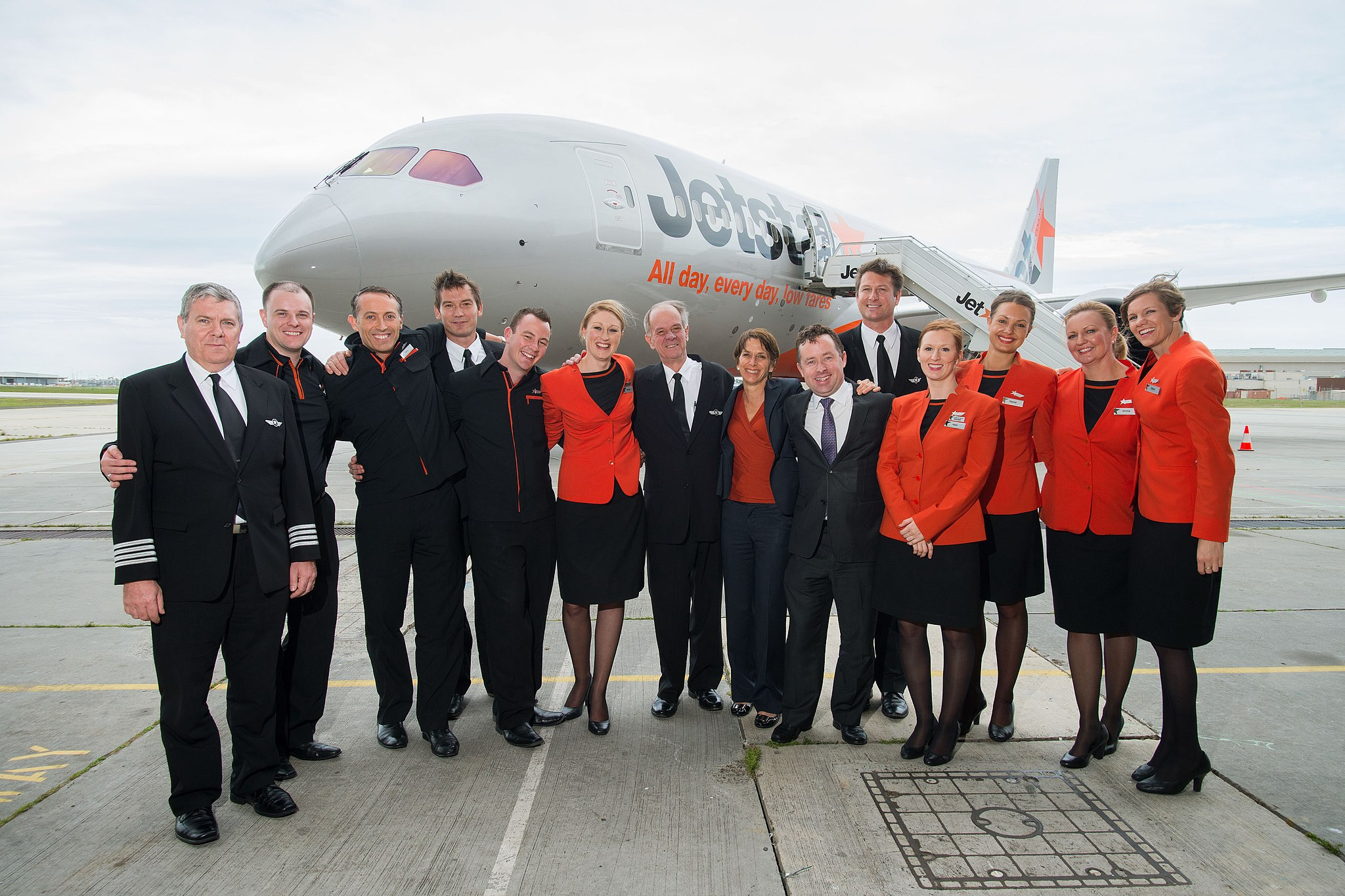Image of a Jetstar Airways flight crew with a 787 Dreamliner behind them.