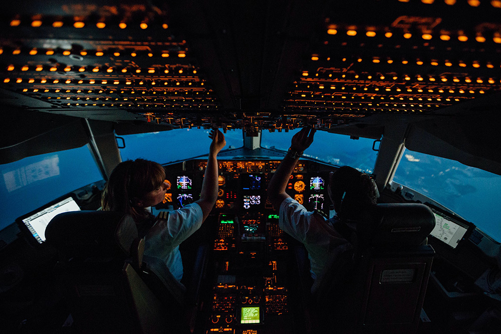 Pilots adjust overhead controls in the cockpit of a plane.