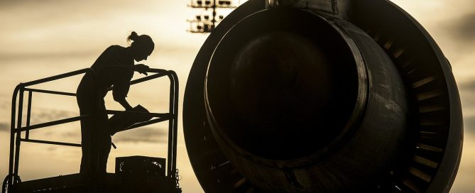 Image of an aircraft mechanic on a lift near an engine at sunset